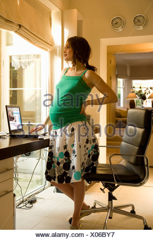 Young pregnant woman standing by desk in home office, side view - Stock Photo