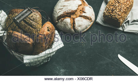 Various bread selection. Rye, wheat and multigrain rustic bread loaves over black background, copy space, horizontal composition - Stock Photo