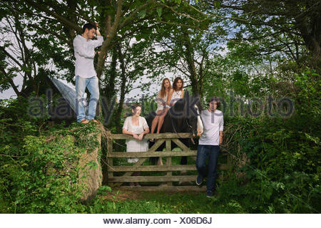 Portrait of five young adults and horse at forest gate - Stock Photo