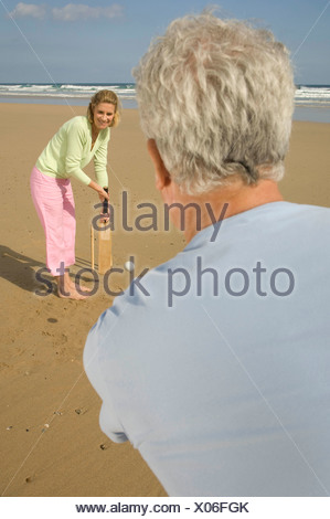 Couple playing cricket on a beach