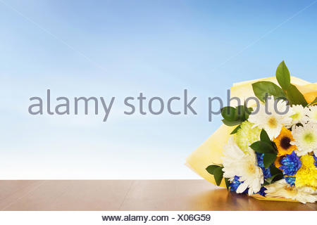 Bouquet of flowers on a wooden surface against blue sky - Stock Photo