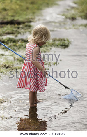 A young girl playing outdoors. - Stock Photo