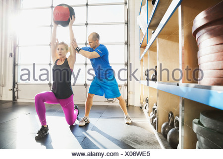 Gym instructor assisting woman with medicine ball lunge - Stock Photo
