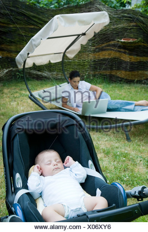 mother working on laptop while baby's sleeping in garden - Stock Photo
