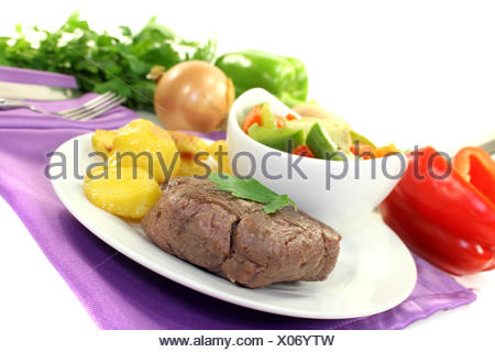 roasted ostrich steaks with baked potatoes - Stock Photo