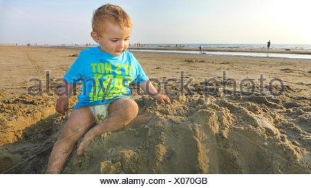 little boy wearing a T-shirt playing on a sandy beach, Netherlands - Stock Photo