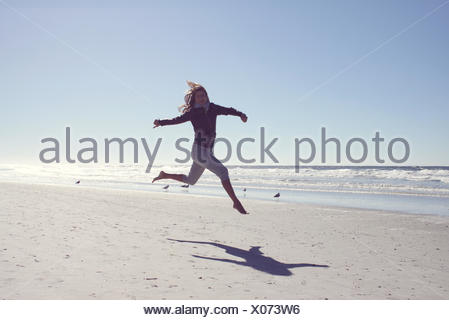 Mature woman running along the beach, Jacksonville, Florida, America, USA - Stock Photo