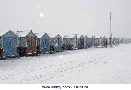 Snow falling on beach huts in Hove, England. - Stock Photo