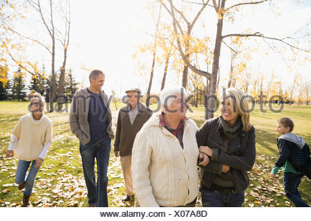 Multi-generation family walking in sunny autumn park - Stock Photo