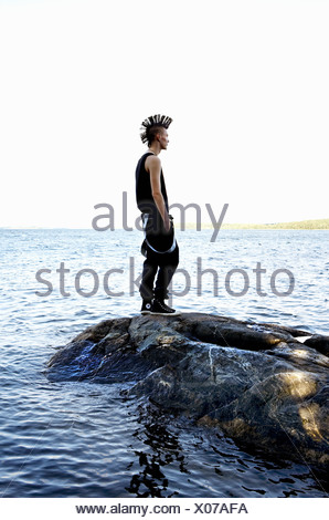 Man with mohawk hairstyle standing on rock and looking at sea - Stock Photo