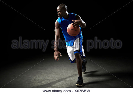 Male basketball player running with ball - Stock Photo