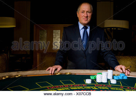 Mature man with cigar at poker table, smiling, portrait - Stock Photo