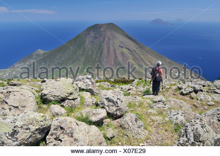 Hiker in front of a volcano on Salina, with the islands of Filicudi and Alicudi at the rear, Aeolian or Lipari Islands, Sicily - Stock Photo