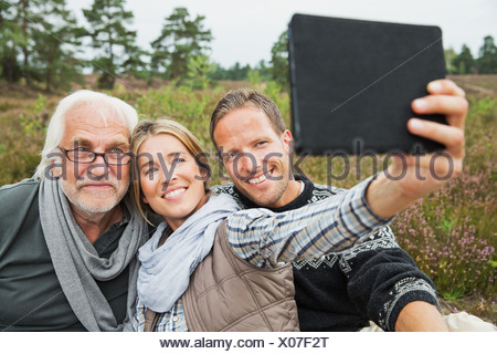 Woman holding digital tablet taking photograph - Stock Photo