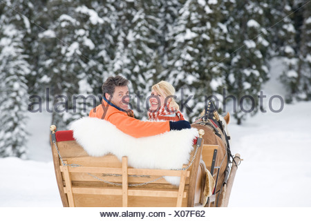 Italy, South Tyrol, Seiseralm, Couple in sleigh, smiling, portrait - Stock Photo