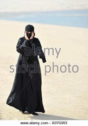 Arab woman in traditional clothing with abayah and veil, Khor Al Udeid Beach, Khor El Deid, Inland Sea, desert miracle of Qatar - Stock Photo