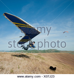 USA, Utah, Lehi, young man taking off with hang glider - Stock Photo