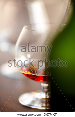 Napoleon Cognac / Brandy in a snifter glass with a wooden background, Montreal, Quebec, Canada. - Stock Photo