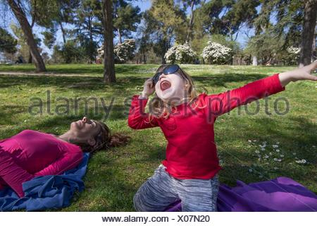 three years old blonde child, with red shirt, sitting on knees in green grass in park, next to mother sleeping, with big adult woman sunglasses - Stock Photo