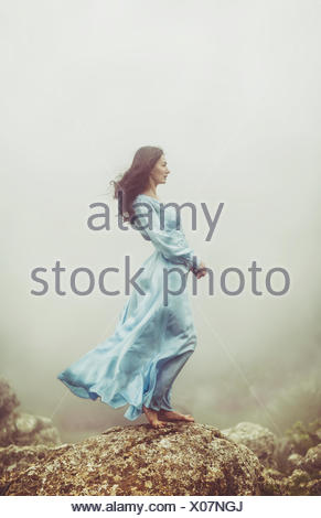 Portrait of a mid adult woman standing on rocks in the mist - Stock Photo