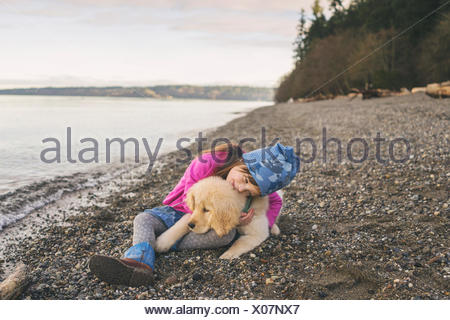 Young girl cuddling with golden retriever puppy on the beach - Stock Photo