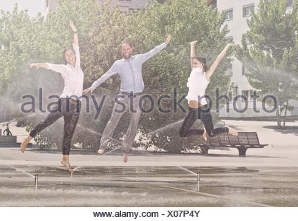 Two women and one man jumping in the park, between water sprinklers, Innsbruck, Tyrol, Austria - Stock Photo