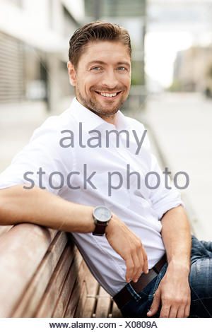 Portrait of smiling man wearing white shirt sitting on wooden bench - Stock Photo