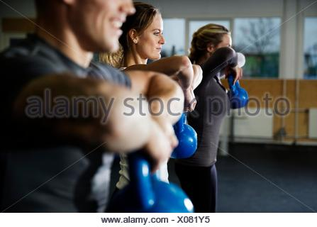 Row of men and women training with kettlebells in gym - Stock Photo