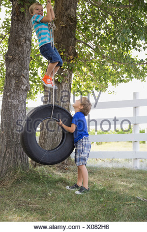 Playful boys playing on tire swing - Stock Photo