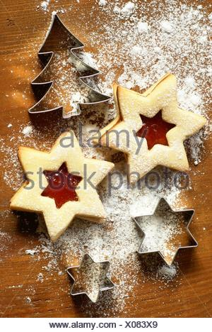 Christmas cookies with jam and cookie cutters on dark wooden background. - Stock Photo