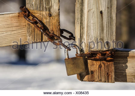 Close-Up Of Padlock Tied Up With Rusty Chain On Wooden Gate - Stock Photo