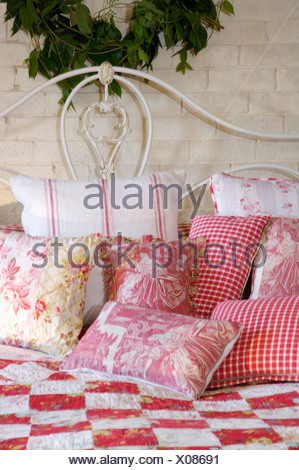Floral cushions and patchwork quilt on bed with wrought iron bedhead ...