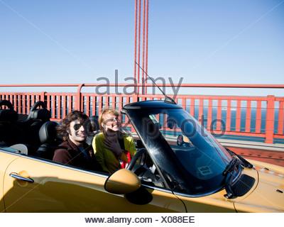 USA, California, San Francisco, young couple passing Golden Gate Bridge in convertible car - Stock Photo