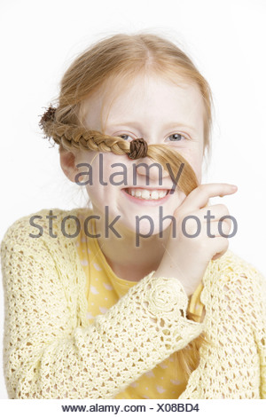 Girl, 8 years old, smiling and holding a braid across her face - Stock Photo