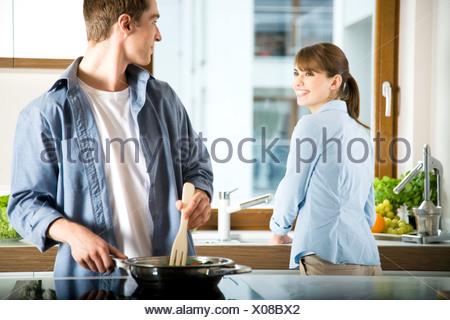 couple working in kitchen - Stock Photo