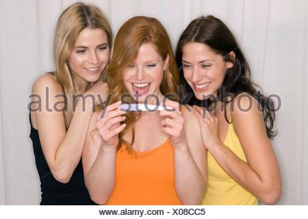 Three women looking at a pregnancy test, studio shot - Stock Photo