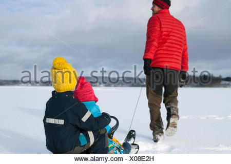 Father pulling sons along on sledge in snow covered landscape, rear view - Stock Photo