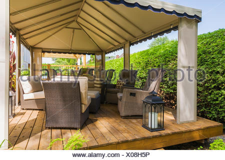 Gazebo on wooden deck furnished with wicker furniture, Quebec, Canada - Stock Photo
