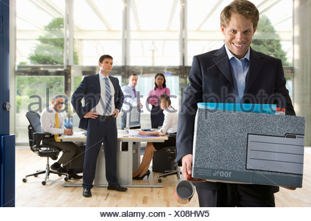 Business people watching smiling businessman leave office with box of belongings - Stock Photo