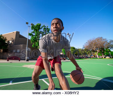 Young man dribbling basketball on outdoors court - Stock Photo