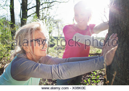 Women in forest leaning against tree stretching - Stock Photo