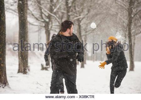 Three friends having a snowball fight - Stock Photo