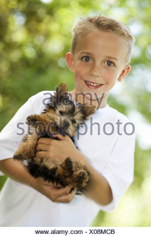 Boy holding small dog - Stock Photo