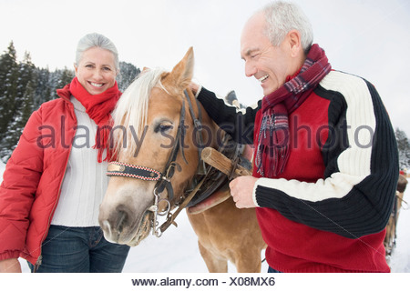 Italy, South Tyrol, Seiseralm, Senior couple standing by horse, smiling, portrait, close-up - Stock Photo