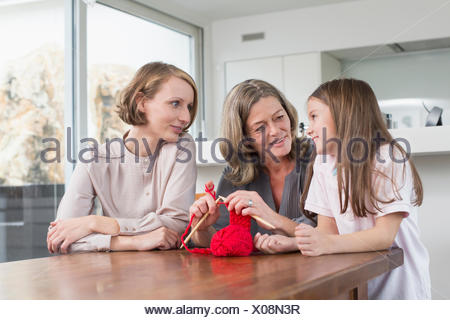 Grandmother, mother and daughter knitting together - Stock Photo