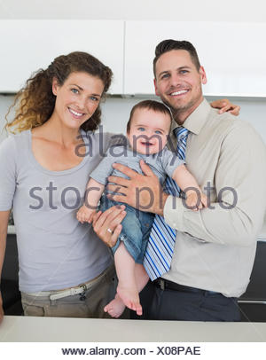 Happy parents with baby in kitchen - Stock Photo