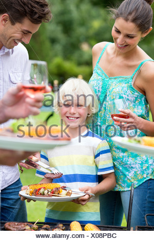 Portrait of smiling boy holding plate of barbecue - Stock Photo