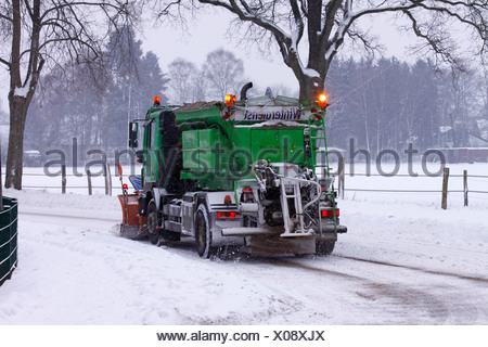Snow-clearing vehicle clearing the road from snow and ice, spreading sand against black ice, - Stock Photo