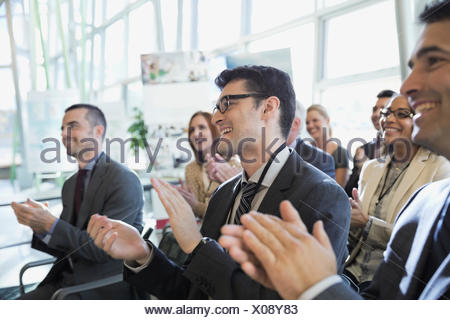Businessmen applauding at conference - Stock Photo
