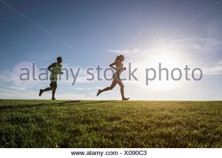 Sunlit man and woman running in park - Stock Photo